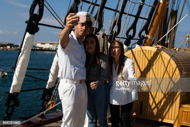 Crew member of Italian sailing ship Amerigo Vespucci takes a selfie with visitors in Naples Italy October on 06 2017