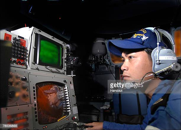 A crew member of Japan Maritime Self Defense Force missile destroyer JS Kongo monitor screens as a Standard Missile 3 is launched from the Japan...