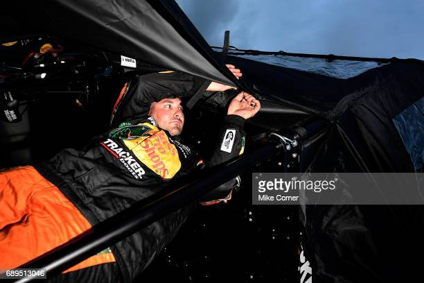 A crew member of the Bass Pro Shops/Tracker Boats Toyota puts on a rain cover during a weather delay during the Monster Energy NASCAR Cup Series...