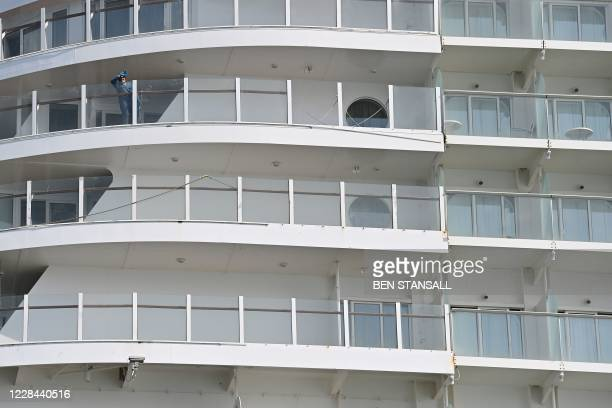 Crew member of the cruise ship 'Allure of the Seas' waves towards passsengers on a Mudeford Ferry's cruise ship tour off the Dorset coast in southern...