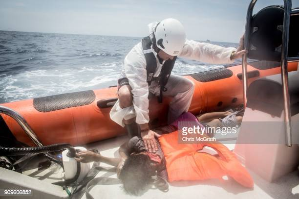 A crew member of the Migrant Offshore Aid Station 'Phoenix' vessel pauses over the body of a man who drowned at sea after a wooden boat bound for...