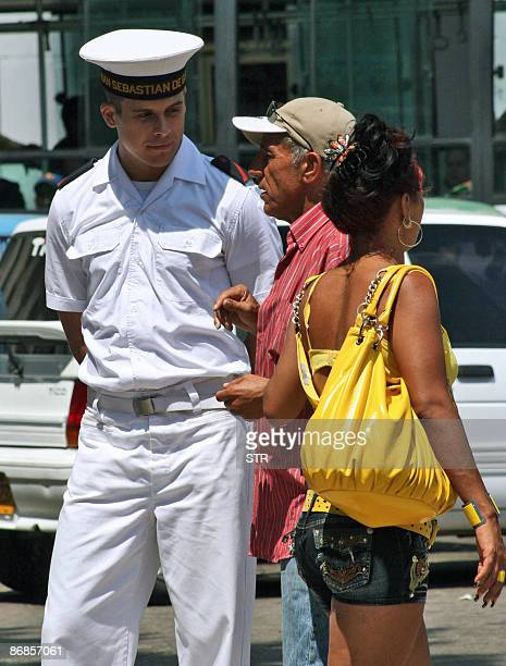 A crew member of the Spanish Navy training ship Juan Sebastian Elcano talks to Cubans in Havana' s Central Park on May 8 2009 The fourmasted tall...