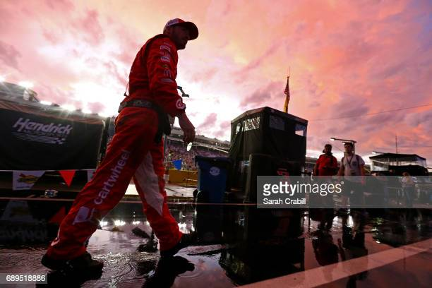 A crew member of the Target Chevrolet walks on the grid during a rain delay during the Monster Energy NASCAR Cup Series CocaCola 600 at Charlotte...
