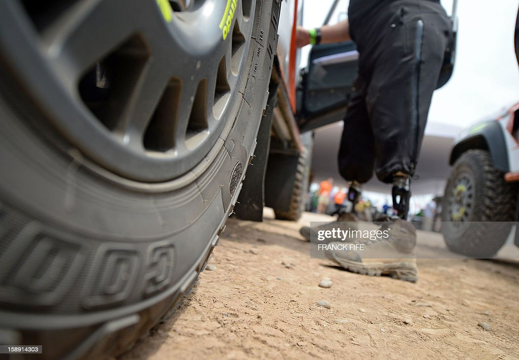 A crew member of the team Race 2 Recovery, consisting of British and US soldiers who have suffered serious injuries in the conflicts in Iraq and Afghanistan in recent years, enters a car in Lima on January 3, 2013, ahead of the 2013 Dakar Rally which this year will thunder through Peru, Argentina and Chile from January 5 to 20.