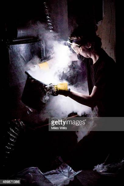 A crew member prepares dry ice behind the scenes during a performance of Mother Goose at Hackney Empire on December 2 2014 in London England