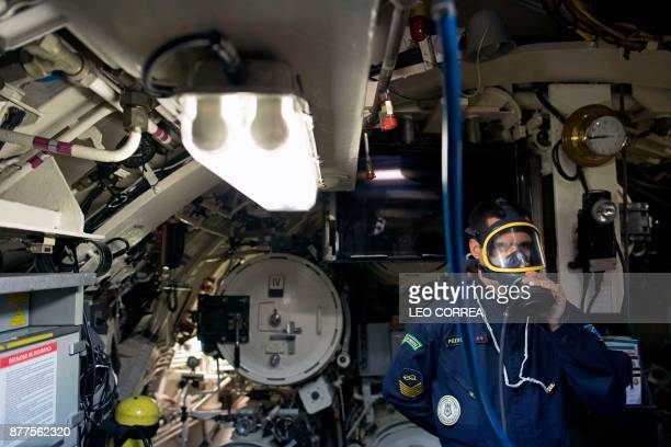 A crew member puts on emergency gear during a presentation to the press inside the Brazilian submarine Timbira in Rio de Janeiro Brazil on November...