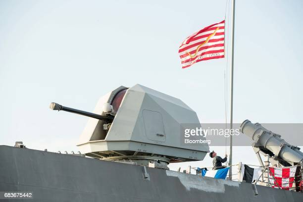 A crew member raises a flag on the US Navy's USS Coronado littoral combat ship at the IMDEX Asia 2017 maritime defence show in Singapore on Tuesday...