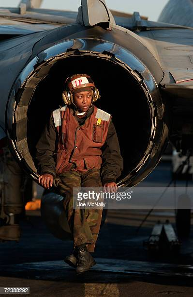 A crew member rests during a gruelling day in the exhaust cone of a F14 February 28 2003 from the carrier USS Abraham Lincoln in the Persian Gulf...