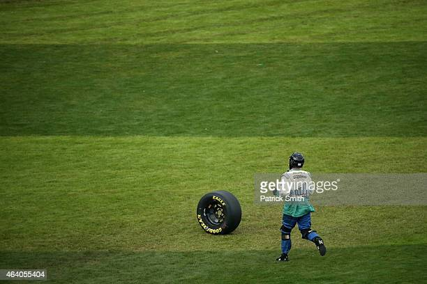 A crew member retrives a loose tire from the infield during the NASCAR XFINITY Series Alert Today Florida 300 at Daytona International Speedway on...