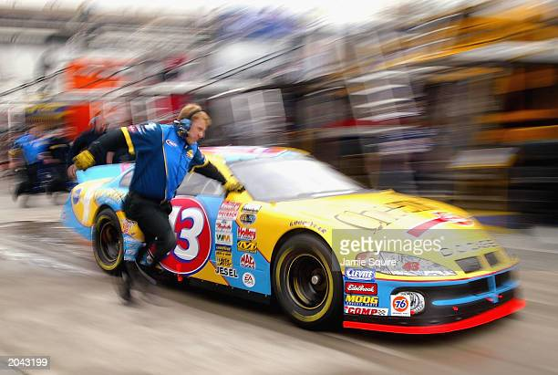 A crew member runs alongside John Andretti's Petty Enterprises Dodge Intrepid R/T during practice for the NASCAR MBNA 500 on March 7 2003 at the...