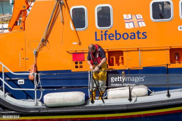 A crew member scecures a buoy to the Royal National Lifeboat Institution RNLI Dover Life boat leaving Folkestone Harbour Folkestone Kent UK