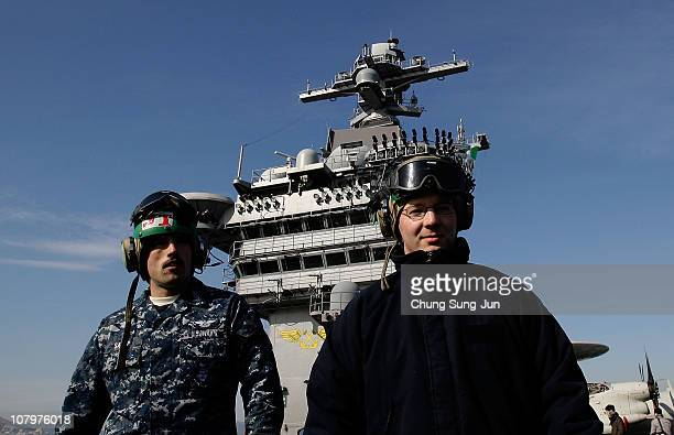 Crew member stand on the flight deck of Aircraft Carrier USS Carl Vinson whilst at anchor in Busan port on January 11 2011 in Busan The USS Carl...