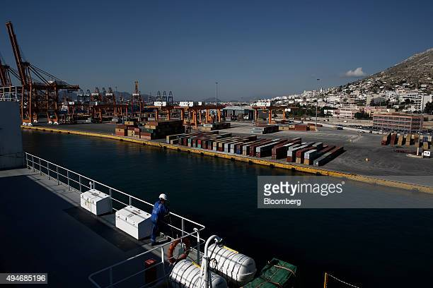 A crew member stands aboard the Topeka vehicle carrier and looks out towards the container section of the Port of Piraeus operated by Piraeus Port...