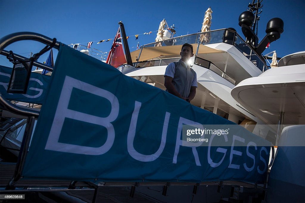 A Crew Member Stands On A Gangway To A Luxury Yacht Built By