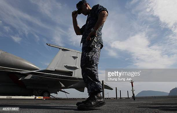 Crew member stands on the flight deck of Aircraft Carrier USS George Washington whilst at anchor in Busan port on July 11 2014 in Busan South Korea...