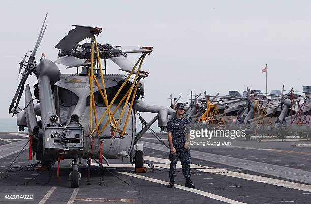 A crew member stands on the flight deck of Aircraft Carrier USS George Washington whilst at anchor in Busan port on July 11 2014 in Busan South Korea...
