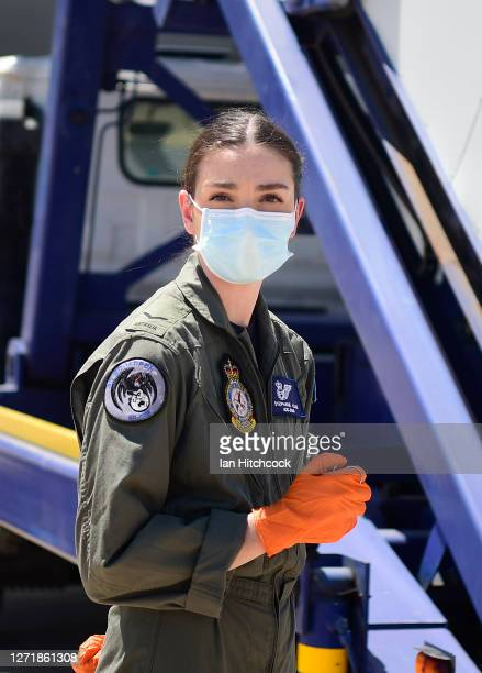 Crew member stands whilst wearing her protective equipment as Australian troops from 3 RAR board a KC 30 aircraft which will take them to Victoria on...