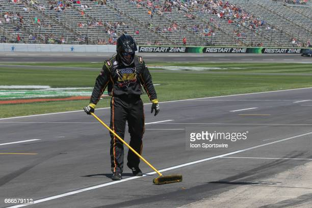 A crew member sweeps the pit stall during the My Bariatric Solutions NASCAR Xfinity Series race on April 8 2017 at Texas Motor Speedway in Fort Worth...