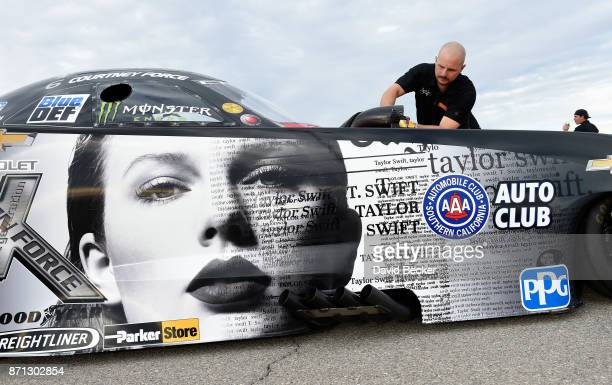 Crew member Tim Fabrisi wipes down NHRA Funny Car driver Courtney Force's Advance Auto Parts Chevrolet Camaro SS funny car as it features the cover...