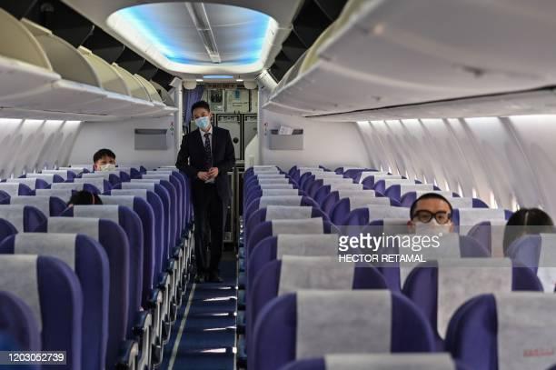 Crew member waits as passengers board their flight to Shanghai at Suvarnabhumi airport in Bangkok, on February 24, 2020. - The novel coronavirus has...
