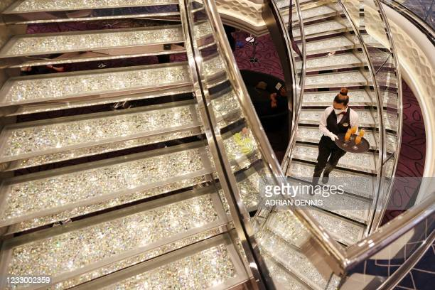 Crew member walks down a crystal staircase on the MSC Virtuosa cruise ship as it prepares to set sail following the easing of Covid-19 restrictions...