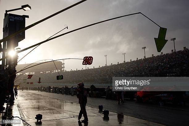 Crew member walks down pit road as rain falls during a red flag rain delay during the NASCAR Sprint Cup Series Ford 400 at Homestead-Miami Speedway...