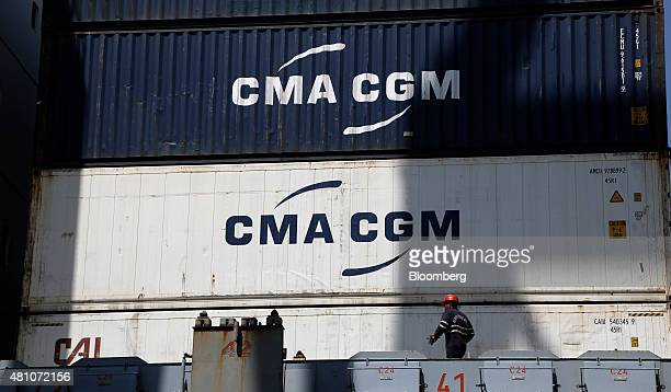 A crew member walks near stacked CMA CGM SA shipping containers aboard cargo ship Santa Bettina operated by Reederei ClausPeter Offen GmbH at...