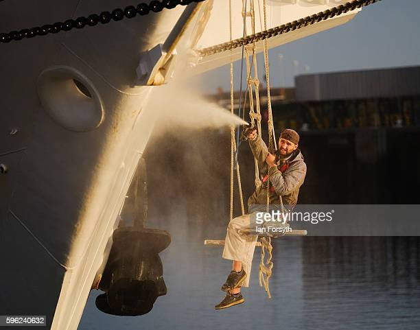 A crew member washes the hull of the Polish ship Dar Mlodziezy during the North Sea Tall Ships Regatta on August 27 2016 in Blyth England The...