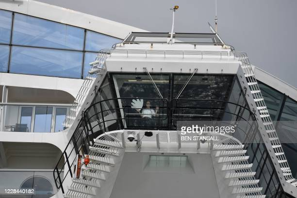 Crew member waves from the cruise ship 'Anthem of the Seas' towards passengers of a Mudeford Ferry's cruise ship tour off the Dorset coast in...
