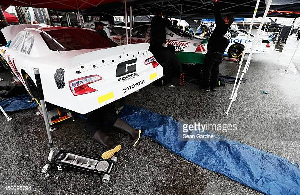 A crew member works on the Bassett Racing Chevrolet through a rain delay during practice for the NASCAR KN Pro Series Drive Sober 150 at Dover...