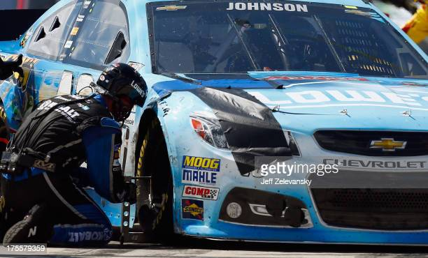 A crew member works on the Lowe's Planes Chevrolet driven by Jimmie Johnson following an incident during the NASCAR Sprint Cup Series GoBowlingcom...