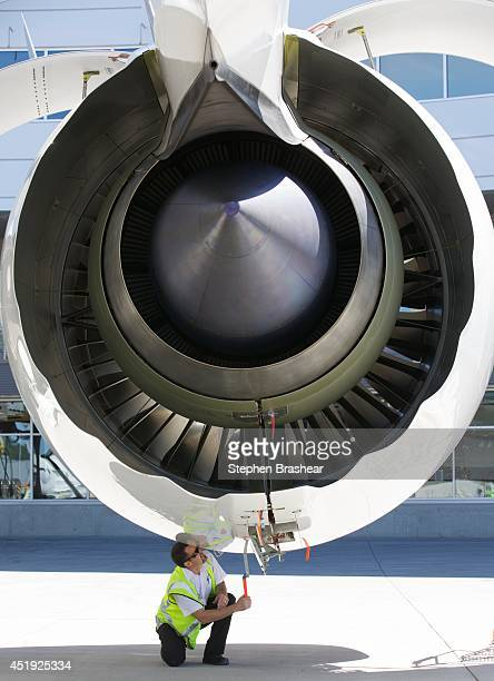 A crew member works on the Rolls Royce engine of an Air New Zealand Boeing 7879 Dreamliner July 9 2014 in Everett Washington The 7879 Dreamliner was...