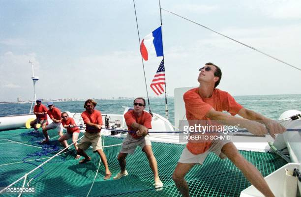 Crew members aboard the 86foot catamaran Explorer help raise a mainsail 29 May 1999 as they take a short practice sail off the coast of Miami Beach...