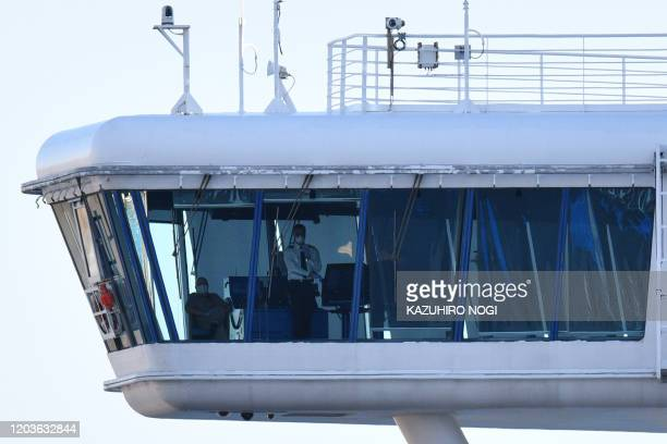 Crew members aboard the Diamond Princess cruise ship are seen at its wheelhouse at the Daikoku Pier Cruise Terminal in Yokohama port on February 27...
