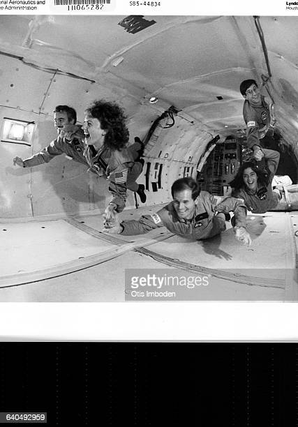 Crew members and backups chosen for the Space Shuttle Challenger mission float in a 'ZeroG' aircraft at NASA's Johnson Space Center in Houston Texas...