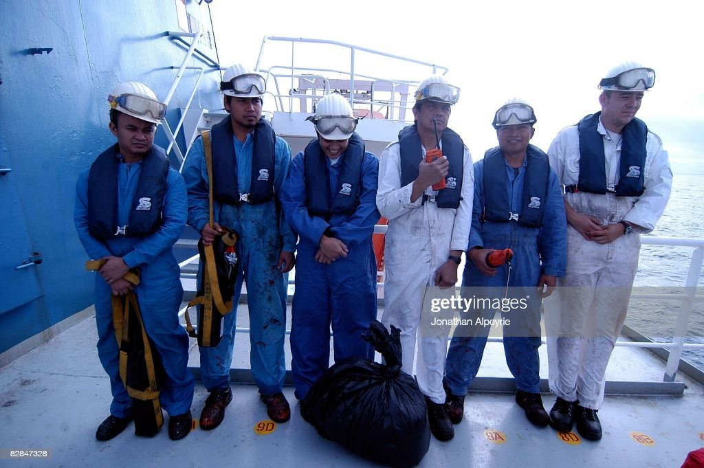 Crew members are waiting to be transfered into the safe raft during a fake fire drill, on July 16, 2008, in France. All crew members are placed in order at the back of the ship before evacuation.