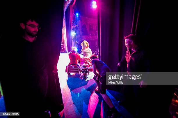 Crew members assist a motorbike and sidecar from stage right during the Puss in Boots pantomime at the Hackney Empire on December 6 2013 in London...