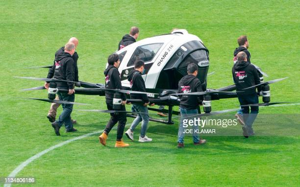 Crew members carry an Air Taxi EHANG 216 during a press preview of FACC AG on Urban Air Mobility at Generali Arena in Vienna Austria on April 4 2019...
