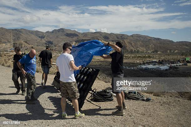Crew members cover lightning equipments at the scenery created in the southern Spanish village of Pechina Almeria province where part of the sixth...