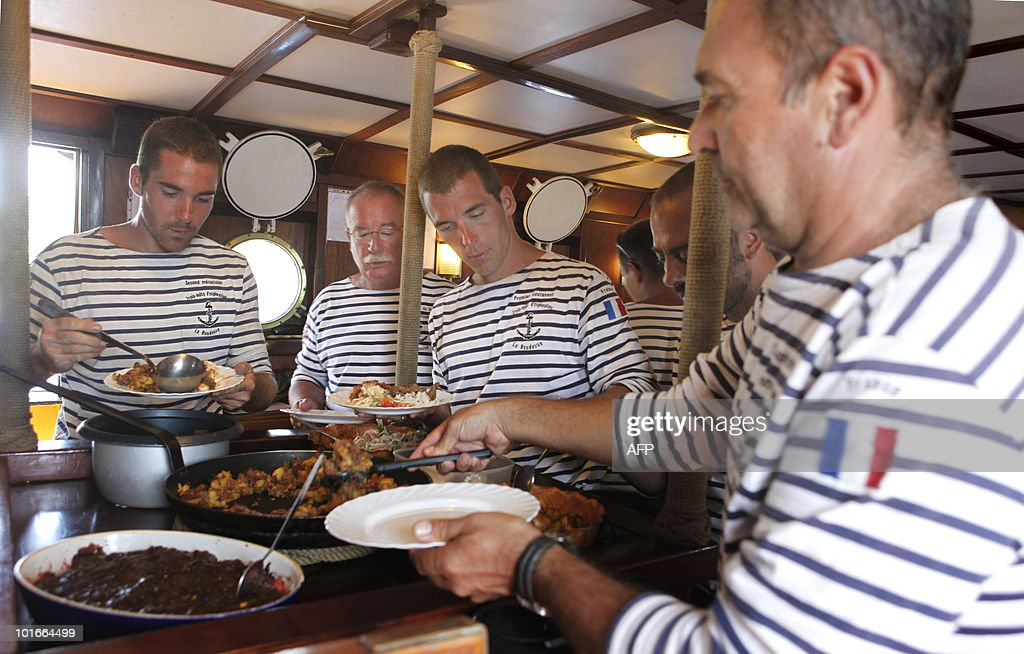 Crew members eat aboard the French schooner La Boudeuse while sailing off the coast of the city of Fort-de-France of the French Caribbean island of Martinique, on June 6, 2010. The three masted ship left the harbour of Fecamp in Brittany last November for a two-year scientific expedition entitled 'Terre-Ocean' (Earth Ocean) from South America to the Pacific Ocean. Patrice Franceschi announced on June 4, 2010 that the expedition around the world of La Boudeuse will end shortly due to lack of funds and that the ship will be sold soon in Martinique.