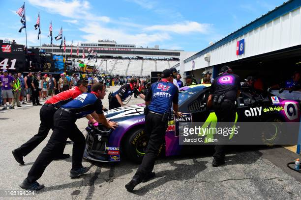 Crew members for Hendrick Motorsports push the Ally Chevrolet backup into the garage stall of Alex Bowman driver of the Axalta Chevrolet during...