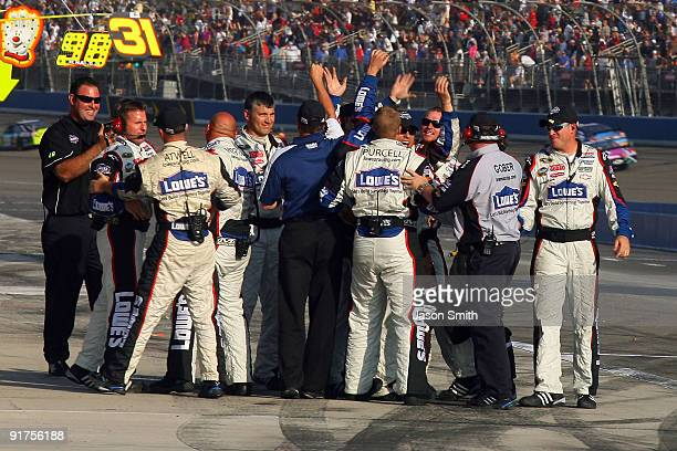 Crew members for Jimmie Johnson driver of the Lowe's Chevrolet celebrate on pit road after winning the NASCAR Sprint Cup Series Pepsi 500 at Auto...