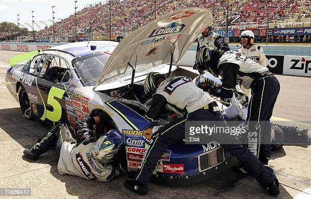 Crew members for Kyle Busch, driver of the Lowe's/Shop Vac Chevrolet, work on his car during a pit stop during the NASCAR Busch Series Zippo 200 on...
