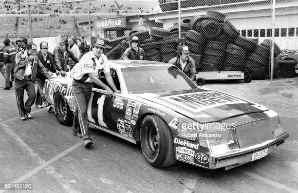 Crew members for NASCAR driver Darrell Waltrip push their racecar to the inspection station prior to the start of the 1982 Daytona 500 at Daytona...