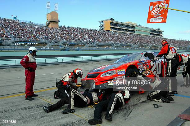 Crew members go to work repairing the Joe Gibbs Racing Home Depot Chevrolet of driver Tony Stewart during the NASCAR Winston Cup Ford 400 on...
