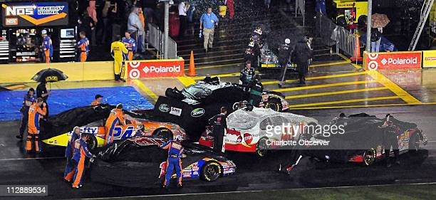 Crew members hurry to push their cars into the NASCAR Nationwide Series garage after the Carquest Auto Parts 300 was called due to rain at Lowe's...