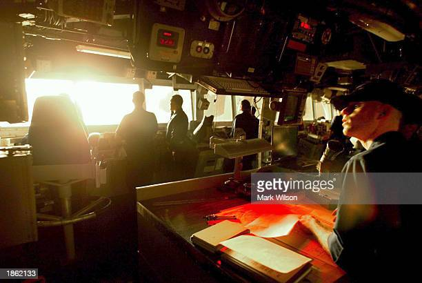 Crew members in the pilot house of the AEGIS guided missile cruiser USS San Jacinto watch a Tomahawk cruise missile take off from a launcher on the...