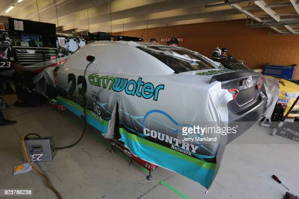 Crew members install a wrap on the car of Gray Gaulding Jr driver of the Earthwater Toyota during practice for the Monster Energy NASCAR Cup Series...