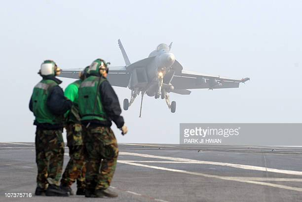 Crew members look at an F/A18E Super Hornet as it lands on the deck of the aircraft carrier USS George Washington during a joint Naval exercise with...