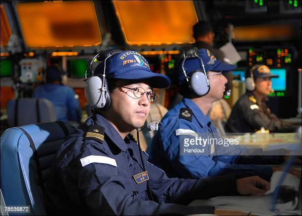 Crew members of Japan Maritime Self Defense Force missile destroyer JS Kongo monitor screens as a Standard Missile 3 is launched from the Japan...